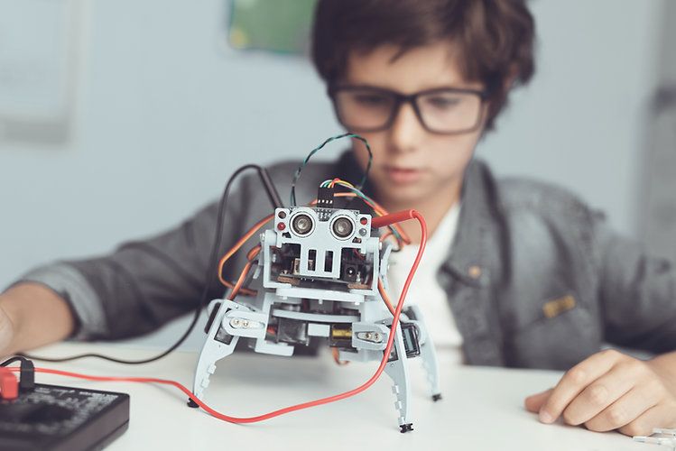 copil care mestereste la un robot la un curs copii de it, robotica si electronica