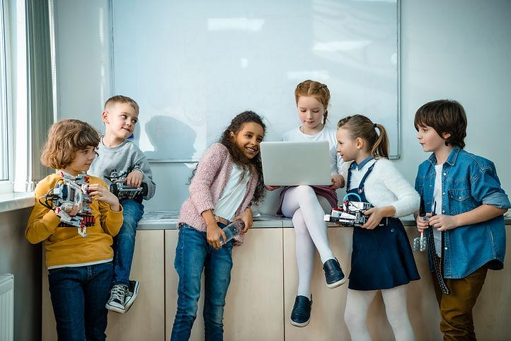 Copii care participa la un curs de robotica si informatica si programeaza roboti
