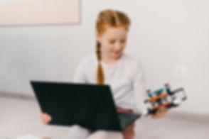 Fetita cu laptopul in brate care se uita la un robot programat la un curs de robotica copii