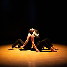 two dancers back to back sit with legs bent under a yellow circle of light