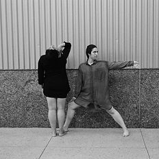 two dancers in dark clothes. one faces away and arches back, one reaches toward the left