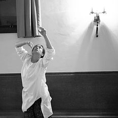 dancer in white tunic looks up and reaches two arms upward