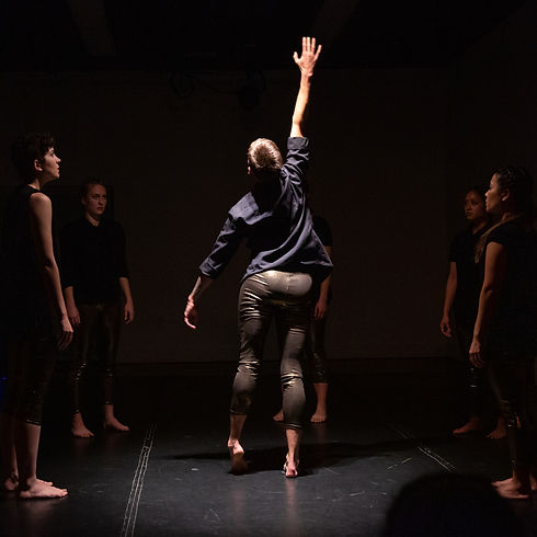 one dancer in black button down and gold leggings reaches toward the sky.
