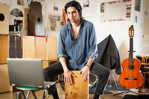 Young gypsy styled man rehearsing and learning new rhythms playing a flamenco drumbox whil