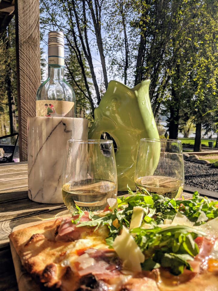 Pizza, a bottle of wine, two glasses and a water pitcher that looks like a fish