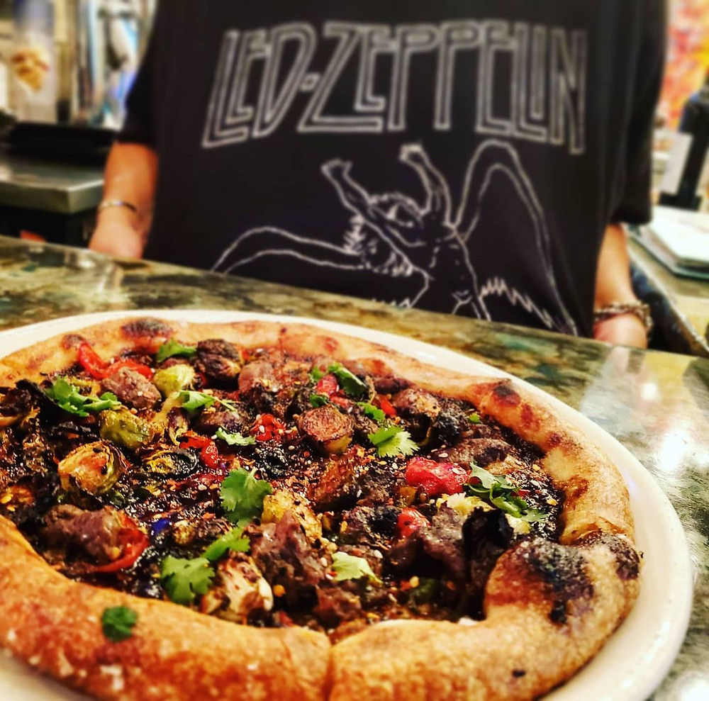 A man in a Led Zeppelin shirt and a pizza