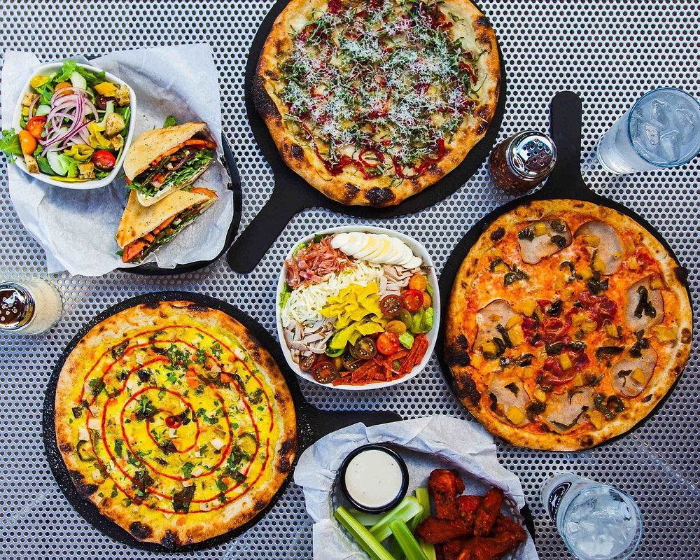 Pizzas and salads arranged on a table