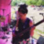 Lilli Elina, female percussionist, pianist, bassist, vocalist, at Wilderness festival, on stage, playing bass.