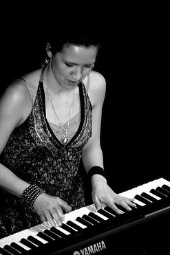 Lilli Elina, female multi-instrumentalist, pianist, percussionist, bassist, vocalist on stage playing the piano.