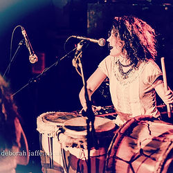 Lilli Elina, London-based girl percussionist, pianist, bassist and vocalist, playing percussion and singing on stage at Hootananny, Brixton, London. Photo by Deborah Jaffe