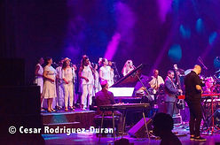 Lilli Elina, multi-instrumentalist, pianist, percussionist, bassist, vocalist, singing with London Lucumi Choir on stage at Barbican Centre with a salsa band.