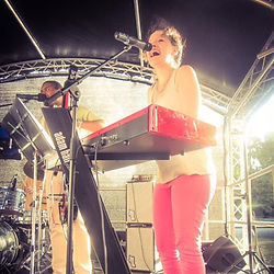 Lilli Elina, London based female pianist, percussionist, bassist and vocalist, on stage, at an outdoor festival with a salsa band, playing piano.