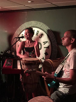 Lilli Elina, percussionist, pianist, bassist, vocalist, singing and playing percussion with Penya on stage at upstairs at Ritzy, Brixton, London