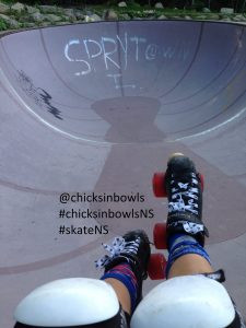 View of legs, kneepads to skates, hanging over the lip of a bowl at the skate park. Hashtags for chicksinbowls