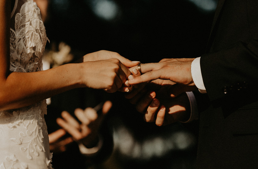 bride putting ring on husbands finger