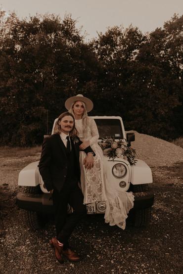 bride and groom posing on car