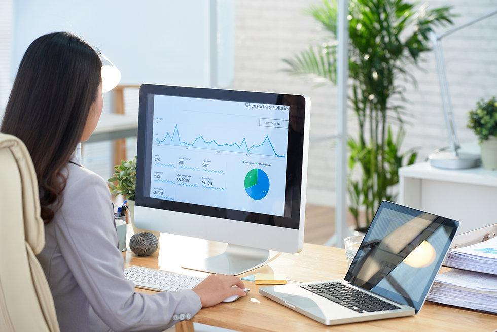 asian-businesswoman-sitting-desk-office-studying-graphs-large-computer-screen.jpg