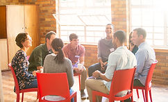 People sitting red chairs in a circle having a group therapy session
