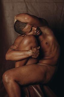 René Loui, homem negro, desnudo, abraça o joelho direito e envolve sua cabeça com o braço esquerdo.