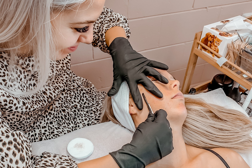 Beauty therapist applying dermaplaning treatment