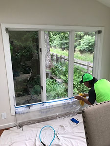 installing window film to a sun room near dining room table