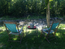 Lawn chairs and wine creekside