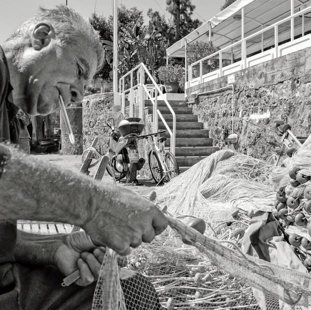 Pescatore mentre sistema la rete