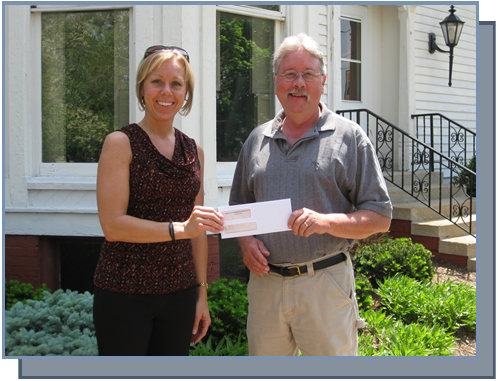 Director Terry Hensley presents a check to board member Donna McVay in 2015.