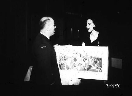 A young woman, Nancy Burden, presenting a drawing of the RCAF to be painted inside Union Station.