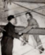 Artists Allen Wargon and Joy Bain sit on scaffolding for a war mural inside Union Station in 1944.