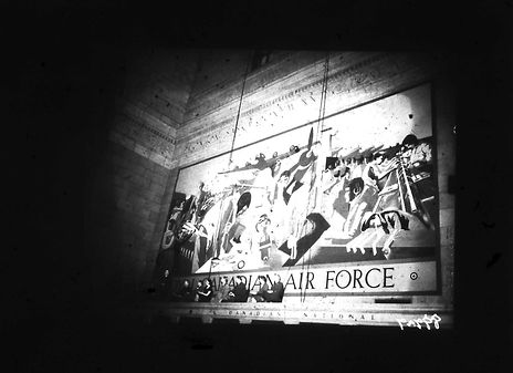 A black and white photograph of a large air force-themed painting on the wall of Toronto's Union Station in 1944.