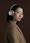 Girl stares at camera with an ambiguous yet bold expression, wearing large white headphones