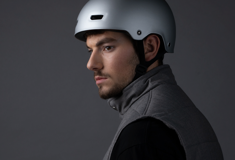 Man in a silver helmet looks thoughtfully over his left shoulder.