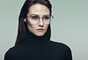 Dark haired woman wearing stylish glasses and a black turtle neck sweater.