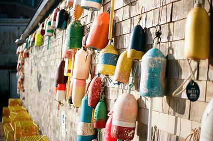 cedar shingle wall with many buoys tied to it