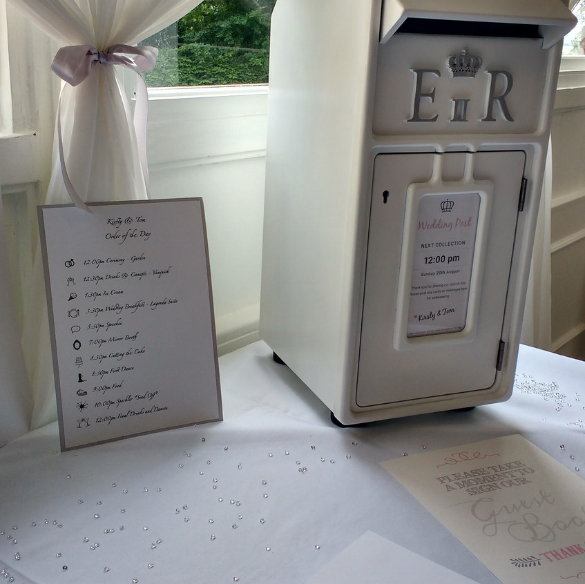 post box and order of the day card on gift table at wedding