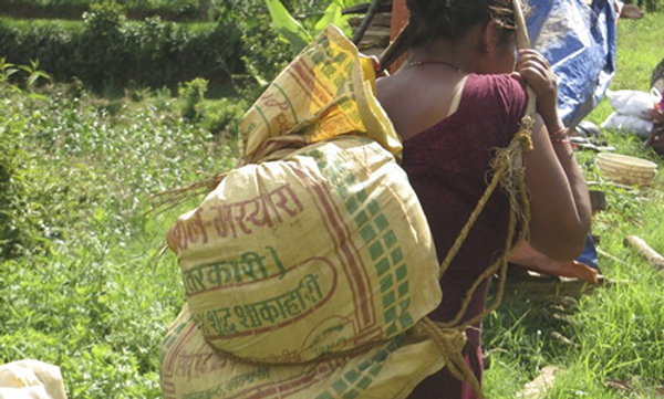A young woman carrying a bag of emergency food ration for her family.