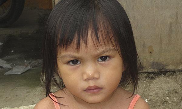 A small Filipino girl looking sad.
