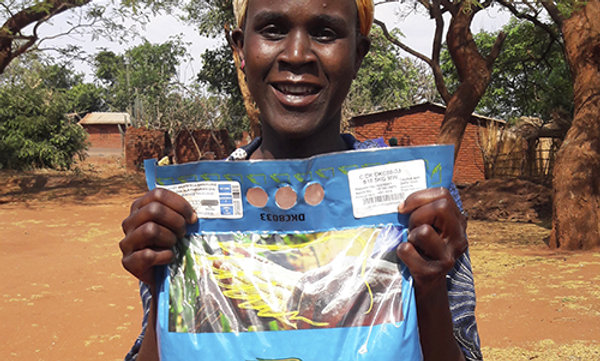 A happy woman holding up a bag of seeds.
