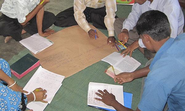 A teacher instructing a group of men.