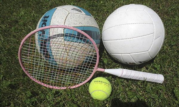 Two volleyballs, a badminton racquet and a tennis ball on grass.