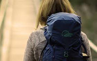 A young girl with blue backpack walking alone.