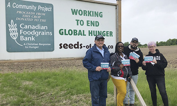 Supporters standing in front of Seeds of Life program sign.