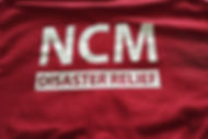 NCM Disaster Relief logo on red t-shirt.