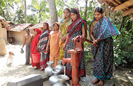 A group of women standing while a woman pumping water into a jug.