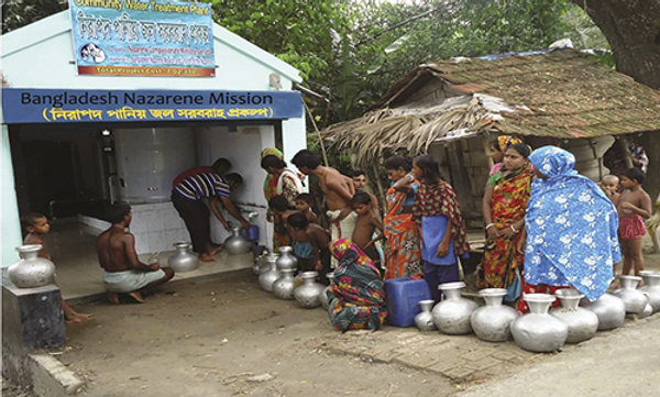People in line with jugs waiting to get clean water from a faucet.