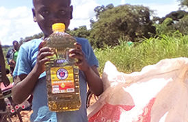 A young boy holding a bottle of cooking oil.