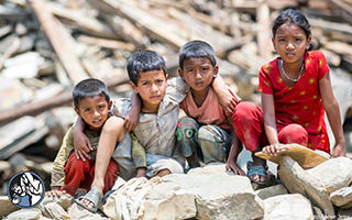Four children sitting on rubble.