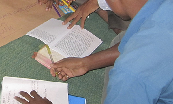 A student reading notes and the Bible.