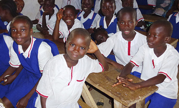 Students wearing school uniforms sitting in a classroom.